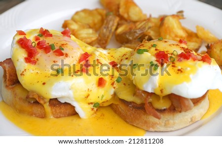 English breakfast Eggs Benedict. Muffins, bacon, poached eggs, and buttery hollanda sauce serve with potato fried - stock photo