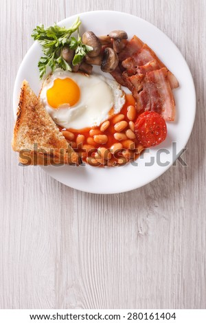 English breakfast: fried egg, bacon, beans and toast on a plate close-up. Vertical view from above  - stock photo