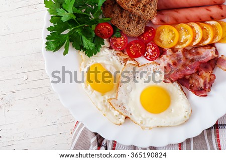 English breakfast - fried eggs, bacon, sausages and toasted rye bread. Top view - stock photo
