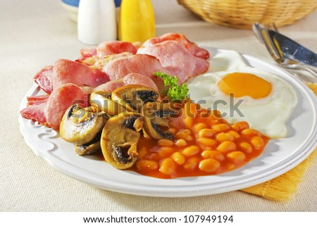 English breakfast of bacon, egg, baked beans and mushrooms. . - stock photo