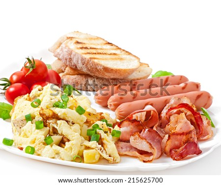 English breakfast - scrambled eggs, bacon, sausage and toast - stock photo