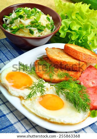 English breakfast, scrambled eggs with toasts, bacon, ham and vegetamles. Salad with cabbage, cucumber. - stock photo