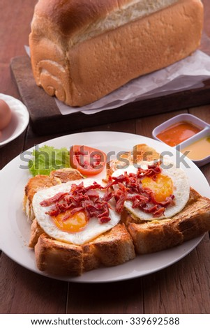 English Breakfast: toast, sunny side up eggs, bacon, ham and salad - stock photo