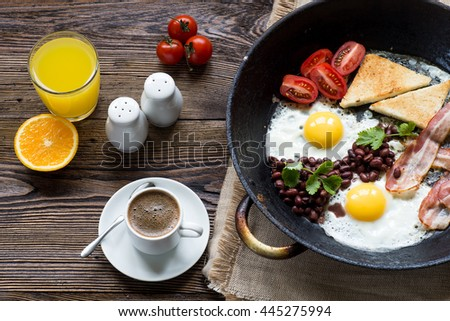English breakfast with bacon, sausage, fried egg, baked beans on C ...