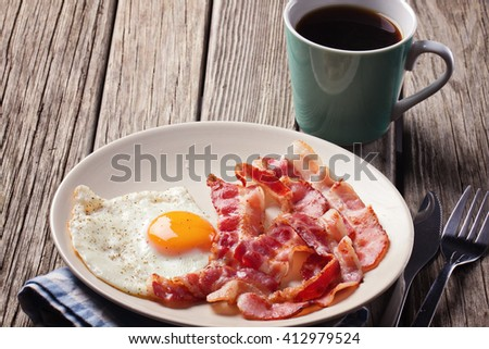 English breakfast with fried eggs and bacon, cup of coffee - stock photo
