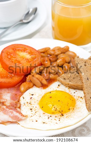 English breakfast with fried eggs, bacon, beans, toasts, close-up - stock photo