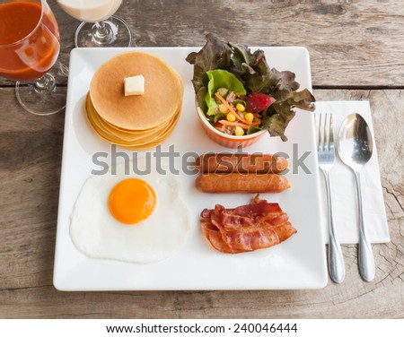 English breakfast with fried eggs, bacon, sausages and salad on  - stock photo