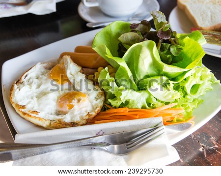 English breakfast with fried eggs, bacon, sausages, beans, toasts and fresh salad - stock photo