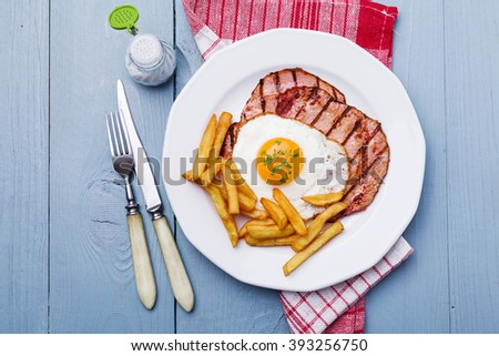 English breakfast with grilled ham, fried egg and french fries. - stock photo