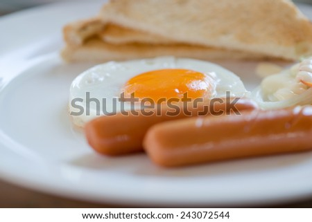 English breakfast with sausage, eggs  bread  and salad - stock photo