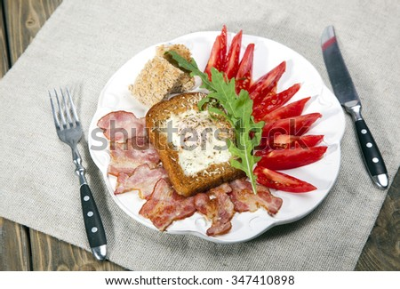 English breakfast with tomatoes, bacon, toasts and fresh salad on a white plate