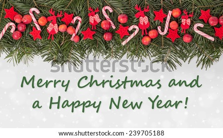 english Christmas card with Pine green, candy Canes, apples and text Merry Christmas and a happy New Year/Merry Christmas and a happy New Year/english - stock photo