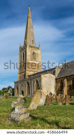 English Country Church with Graveyard and Tall Spire on Summers Day against blue cloud studded sky - stock photo