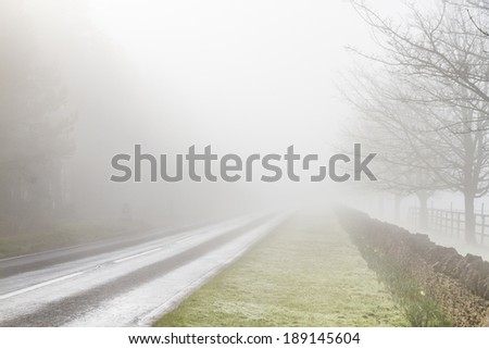 English country road disappearing into fog - stock photo