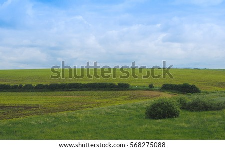 English countryside seen from a train near Liverpool, with selective focus on the horizon and motion blur on the foreground