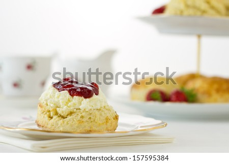 English Cream tea scene with scone offset, Devonshire style, on china plate with cake stand behind. Part of a series showing the preparation of scones. - stock photo