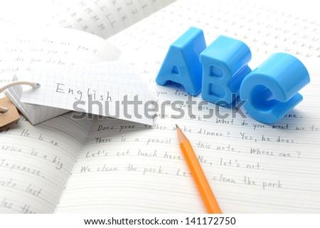 English education, alphabet toy on notebook - stock photo
