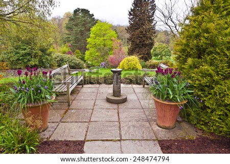English flagged garden with sundial and tulips in terracotta planters in early spring. - stock photo