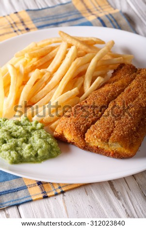 English food: fried fish fillets and chips and pea puree close-up on a plate. Vertical - stock photo