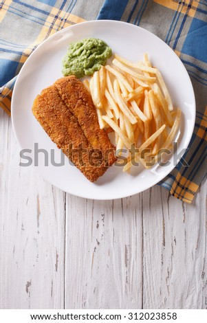 English food: fried fish in batter with chips and pea puree on a plate. vertical top view - stock photo