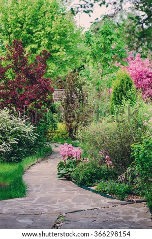 English garden in spring. Beautiful view with blooming trees and shrubs. Stone pathway. - stock photo