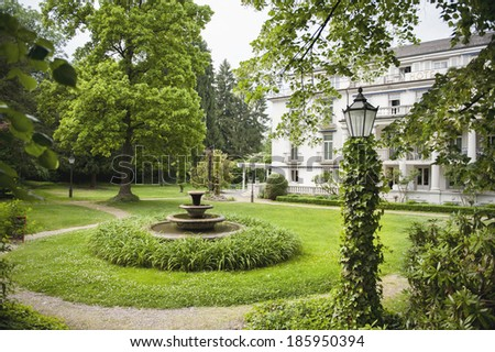 English garden with hotel in the background on spring day - stock photo