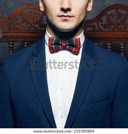 English gentleman beauty concept. Half-face portrait of young man in blue jacket, Scottish bow tie and white shirt posing over vintage screen. Close up. Studio shot - stock photo
