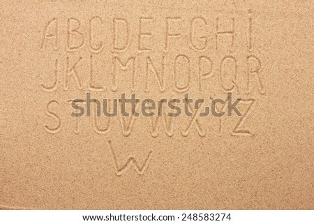 English, German, Portuguese alphabet  written on the sand, as background - stock photo