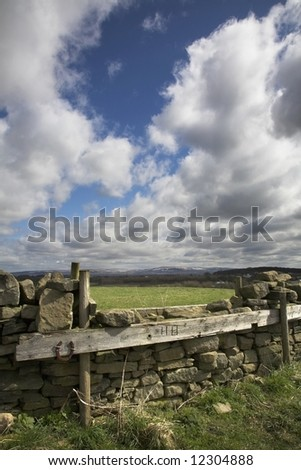 English Hunt jump over stone wall with Pennines in the distance