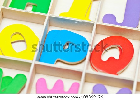 English letters are made of wood on a white background.