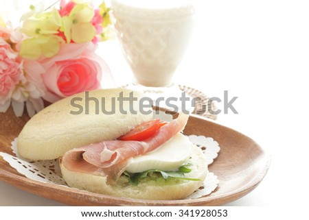 English muffin and ham sandwich with milk