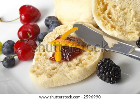English muffin with jam and assorted fruits. - stock photo