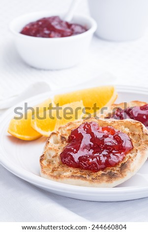 English muffins with strawberry preserves on white dish - stock photo