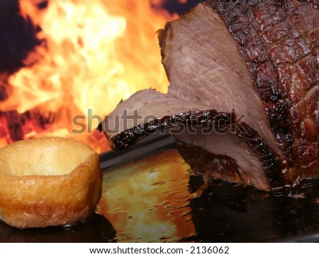 English roast meat by fire with flames, traditionally eaten with yorkshire pudding, macro - stock photo
