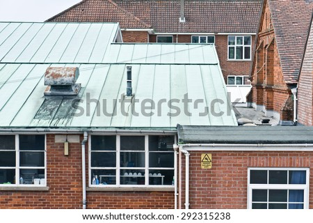 English school buildings with red bricks and tiled roofs - stock photo