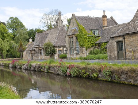 English stone cottages in the traditional Cotswold style, along banks of  river  Eye surrounded by wild flowers .