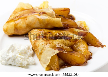 English-style pancakes filled with caramelised pears, topped with light caramel sauce and served with yoghurt. - stock photo