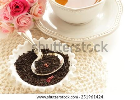 English tea, black tea leaves and rose - stock photo