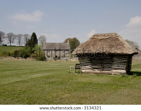 English Village Green with Farmhouse in the background and thatched structure in the foreground