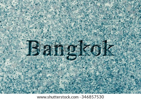 Engraving spelling the city Bangkok on textured old surface