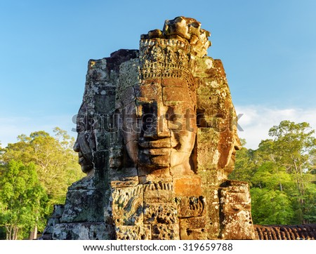Enigmatic face-tower of ancient Bayon temple in evening sun. Mysterious Bayon temple nestled among rainforest in Angkor Thom, Siem Reap, Cambodia. Amazing Angkor Thom is a popular tourist attraction. - stock photo