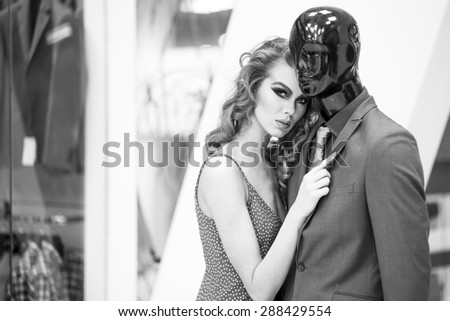 Enigmatic young woman with bright makeup and curly hair standing with male mannequin in formal clothes on shopping background black and white, horizontal picture