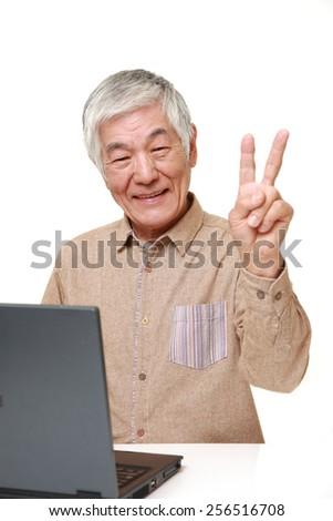 enior Japanese  man using laptop computer - stock photo