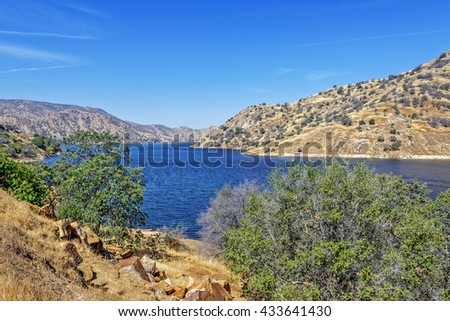 Enjoy blue skies & water at Lake Kaweah Marina, patio boats, fishing boats, and paddle boards are available for rent. Lake Kaweah is a small town which sits at the entrance to Sequoia National Park. - stock photo
