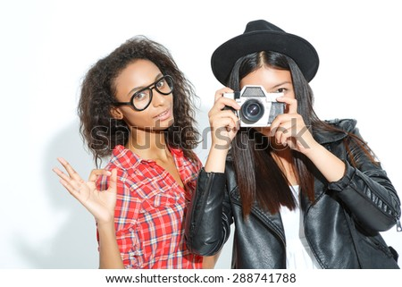 Enjoy  every moment. One girl holding camera and making pictures with her friend standing beside and having fun. - stock photo