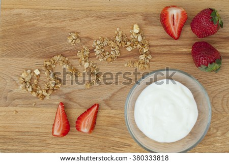 enjoy lettering from muesli and strawberries with yogurt  , a delicious dessert with berries and cookies, healthy Breakfast on wooden background, close-up - stock photo
