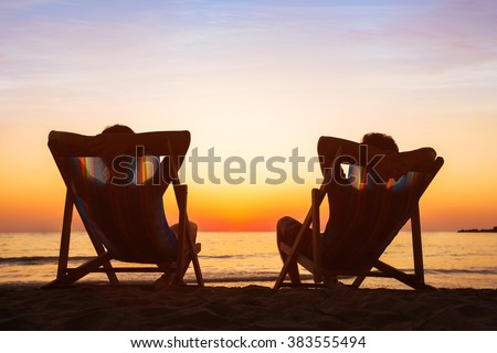 enjoy life concept, couple relaxing in beach hotel at sunset, happy people on honeymoon, paradise travel destination - stock photo