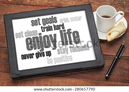 enjoy life - healthy lifestyle word cloud on a digital tablet with a cup of coffee - stock photo