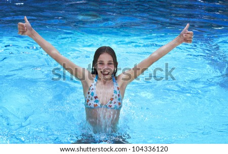Enjoy. Slim young girl smiling happy is spectacularly jumping out of pool with clear blue water