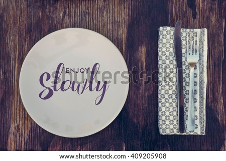 Enjoy slowly quote, healthy eating concept design with restaurant elements over retro style wood surface.  - stock photo